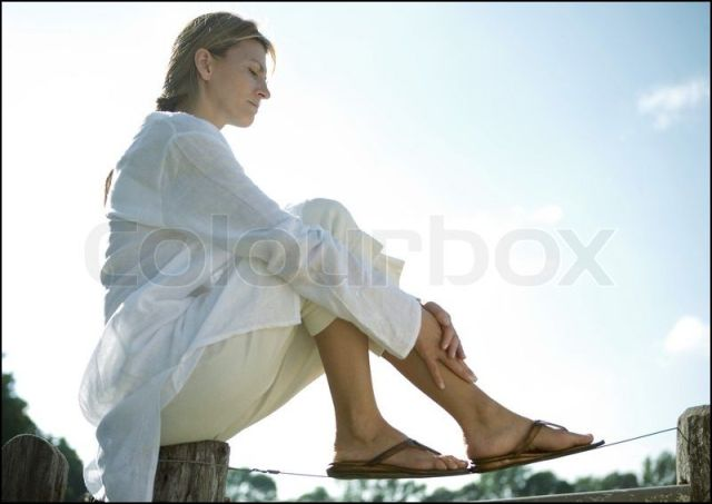 Capture Woman sitting on fence